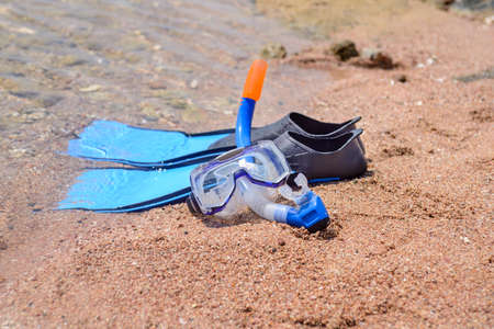 skin diving: Skin diving equipment standing ready on a beach on the sand at the edge of the sea with a pair of flippers, snorkel and goggles, conceptual of recreational activities on summer vacation