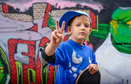 boy skater: Young boy making a V-sign gesture for success and victory, or peace, as he stands in front of a graffiti covered wall holding his skateboard