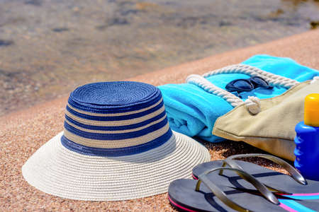 sunhat: Assorted beach accessories on the sand of a tropical beach overlooking the water with a sunhat, sunscreen, towel, thongs, sunglasses and beach bag