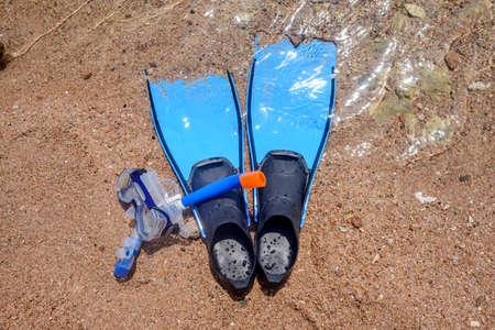 actividades recreativas: Equipos de buceo de la piel de pie listos en una playa en la arena en la orilla del mar con un par de aletas, tubo y gafas, conceptual de las actividades recreativas en las vacaciones de verano