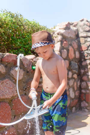 rinsing: Responsible young boy in his swimsuit rinsing off his shoes with a hose to remove excess sand after spending time relaxing on a beach