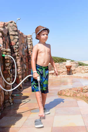 hosepipe: Stylish young boy in a swimsuit and trendy hat standing rinsing off his feet with a hosepipe after visiting the beach at a coastal resort on summer vacation Stock Photo