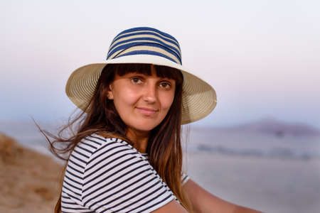 introspective: Close up Pretty Young Woman Wearing Beach Hat, Sitting at the Seaside and Smiling at the Camera.