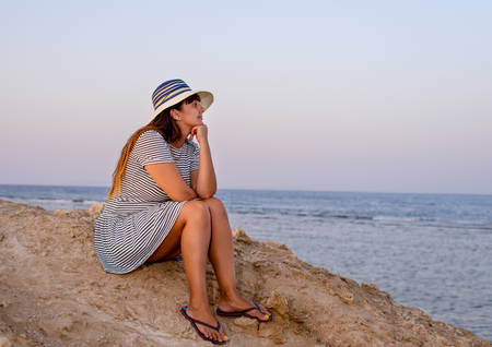 introspective: Romantic young woman wearing hat, striped dress and flip flops while sitting on the shore enjoying the breeze at the seaside in the morning