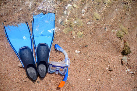 skin diving: Overhead view of skin diving gear lying on a beach with a snorkel, goggles and fins or flippers conceptual of a tropical summer vacation at the seaside