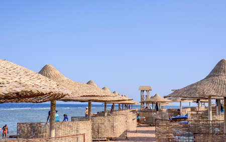 recliner: Thatched beach umbrellas and recliner chairs on a beach at an idyllic tropical resort for a summer vacation, symbolic of travel