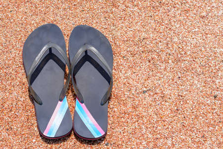 thongs: High Angle View of Pair of Flip Flops Thongs with Colorful Stripes on Sandy Beach Shore Stock Photo