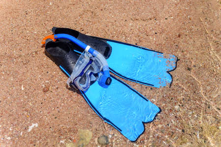 skin diving: View from above of blue rubber flippers and snorkel lying on a sandy beach ready to go skin diving on a summer vacation