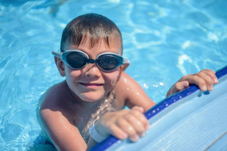 Smiling young boy wearing goggles clinging to the side in a swimming pool grinning happily up at the camera as he enjoys his summer vacation Stock Photo