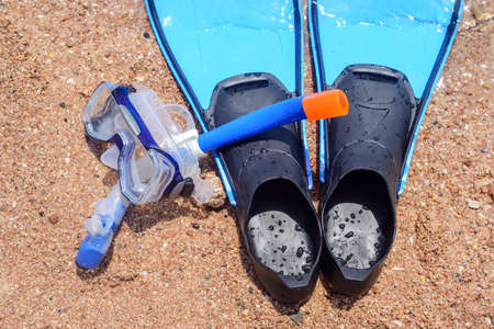 skin diving: Skin diving gear lying ready on the beach with a snorkel, goggles and pair of flippers conceptual of an active summer vacation