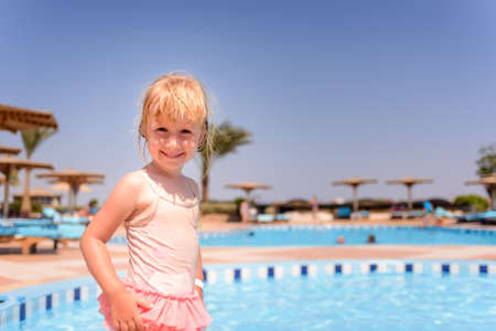 girl with camera: Smiling happy little blond girl at a resort swimming pool standing in her pink swimsuit grinning at the camera on summer vacation, with copyspace