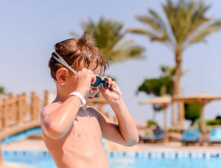 putting on: Young boy putting on his swimming goggles as he prepares to go for a swim in a tropical resort pool on summer vacation