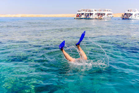tour boats: Snorkeler diving below the surface of the sea viewed from above water so that only his feet and flippers are visible, tour boats in the background