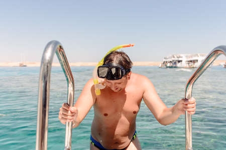 skin diving: Smiling man preparing to go snorkeling standing holding onto the rails on a dive boat with the ocean behind Stock Photo