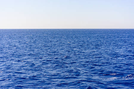 Background texture of a calm deep blue ocean with ripples on the surface of the seawater, full frame