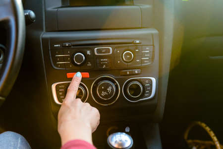 flashers: Female driver pressing a red hazard button on the console of her car to activate emergency flashers in time of trouble Stock Photo