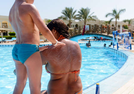 Small boy applying sunscreen on his mother rubbing it into her back and shoulders as she relaxes at the edge of a resort swimming pool on summer vacation