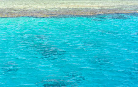 deep water: Crystal clear turquoise blue sea water lapping gently against a sandy shore or sand bank, conceptual of an idyllic summer vacation in the tropics