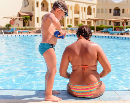 Boy applying sunscreen to his mothers back kneeling down rubbing it in with his hand as she sits at the edge of a resort swimming pool in her bikini