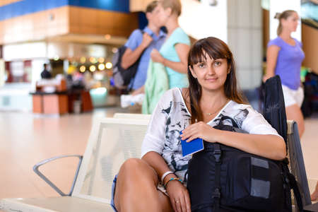 waits: Happy attractive middle-aged woman sitting in an airport lounge with her luggage surrounded by a crowd of passengers as she waits for her flight