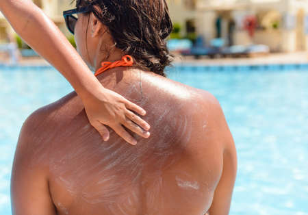 hand rubbing: Young boy rubbing sunscreen onto his mother smearing it over the skin of her back with his hand as she sits in her swimsuit at the edge of a swimming pool Stock Photo