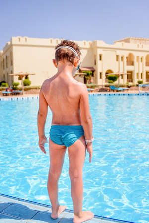 Young boy standing on the edge of a sparkling blue resort swimming pool in his swimsuit and goggles preparing to dive in, back to the camera