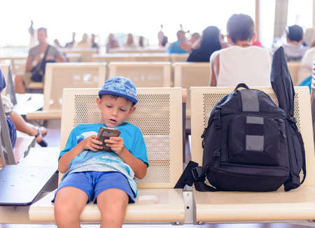 preteen boys: Young boy sitting in an airport terminal waiting for his flight playing on a tablet or mobile phone with a large backpack alongside him Stock Photo