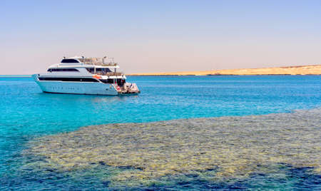 Pleasure boat or tour boat moored off an offshore shallow sand bank and reef for skin diving in a calm blue tropical ocean on a summer vacation Standard-Bild