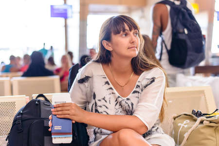 alongside: Woman sitting waiting for her flight with her luggage on the seats alongside her and boarding pass in her hand