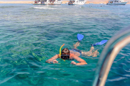skin diving: Man enjoying his summer vacation in the tropics skin diving off a tour boat floating face down in the water viewing the marine creatures below with additional tour boats visible in the background Stock Photo
