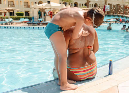 child swimsuit: Small boy rubbing sunscreen onto his Mum applying it to her back as she sits in her bikini at the edge of a resort swimming pool Stock Photo