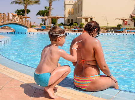 sunscreen: Boy applying sunscreen to his mothers back kneeling down rubbing it in with his hand as she sits at the edge of a resort swimming pool in her bikini