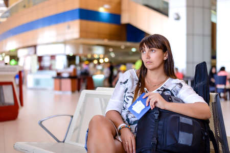 tedious: Happy attractive middle-aged woman sitting in an airport lounge with her luggage surrounded by a crowd of passengers as she waits for her flight