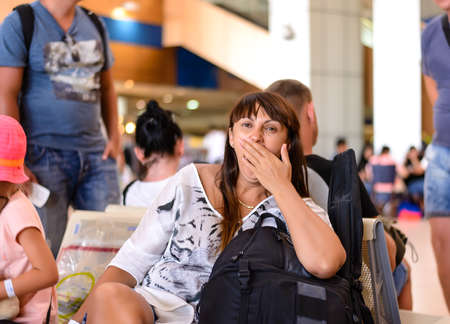 tedious: Bored woman yawning as she waits for her flight while sitting on the chairs in an airport terminal with her luggage