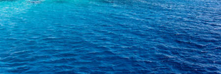 seawater: Background texture of a calm deep blue ocean with ripples on the surface of the seawater, full frame