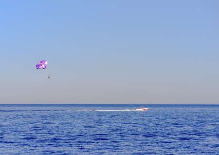 towing: Motorboat towing a parasail parachute with a suspended person in a harness high in the air across a calm blue ocean in evening light