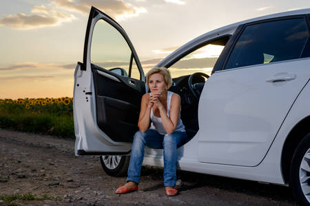 roadside assistance: Woman sitting waiting for roadside assistance in the open door of her car parked on a rural road at sunset staring glumly ahead