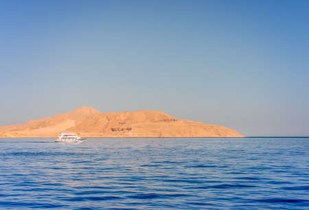 skin diving: Pleasure boat or tour boat moored off an offshore shallow sand bank and reef for skin diving in a calm blue tropical ocean on a summer vacation Stock Photo