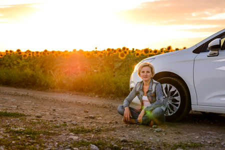Woman waiting beside her car on a rural road at sunset sitting on the ground with her back to the wheel with sunflowers and a fiery orange sky behind her Stock Photo