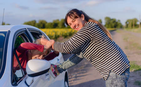 playful behaviour: Playful Woman Pulling the Hair of a Female Driver Inside the Car While Looking at the Side Mirror.