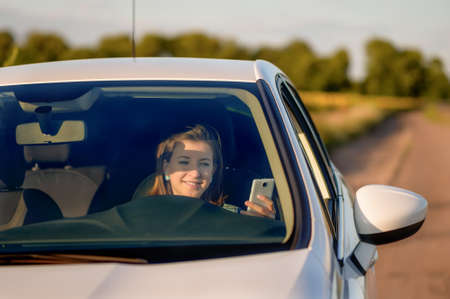 Front View of Teenage Girl Holding Cell Phone While Driving Car on Country Road - Distracted Teenage Driver Texting Behind Wheel in White Car