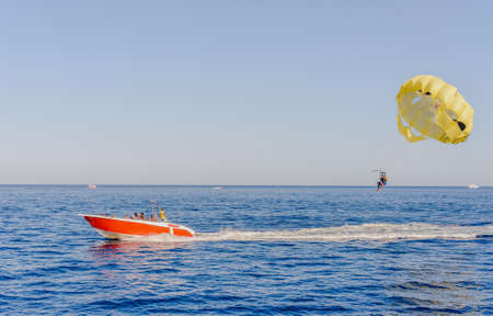 towing: Parasailing on a calm blue ocean with a red motorboat towing a person suspended below a parachute by a harness