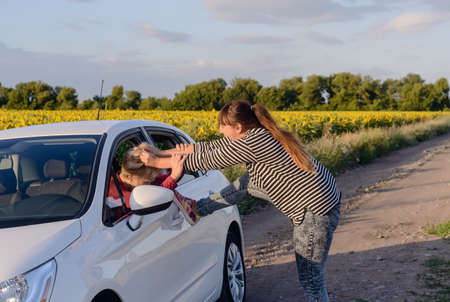 retaliation: Aggressive Woman Pulling the Hair of a Female Driver inside a Car at the Driveway.