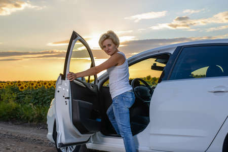roadside assistance: Glum woman sitting in the open door of her vehicle waiting for roadside assistance at the side of a rural road in farmland alongside sunflowers at sunset Stock Photo