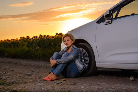 sitting on the ground: Woman waiting beside her car on a rural road at sunset sitting on the ground with her back to the wheel with sunflowers and a fiery orange sky behind her Stock Photo