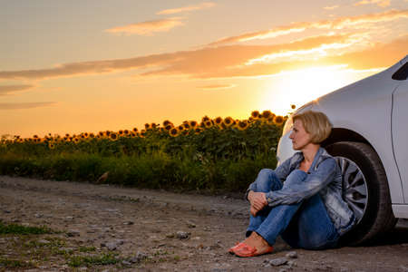 car trouble: Full Length of Blond Woman Sitting on Ground Leaning Against Car on Dirt Road Surrounded by Sunflower Fields at Sunset with Warm Sunlight - Woman with Car Trouble