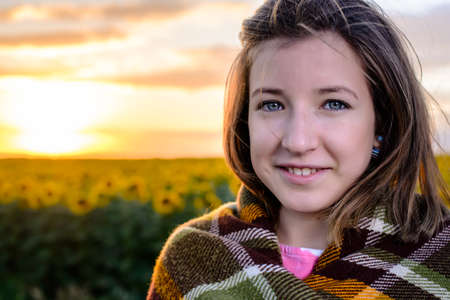 healthy girl: Head and Shoulders Portrait of Brunette Girl Wrapped in Plaid Blanket and Smiling at Camera in front of Sunflower Field at Sunset with Warm Golden Sun and Copy Space Stock Photo