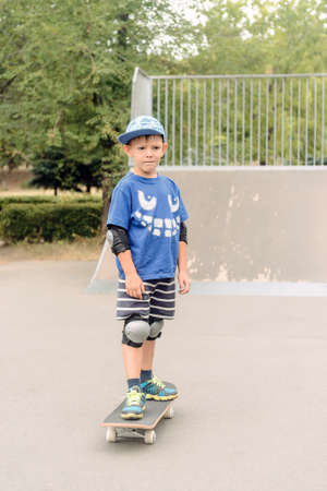 skate park: Small boy standing on his skateboard at the skate park in a trendy blue outfit with protective gear looking at the camera Stock Photo