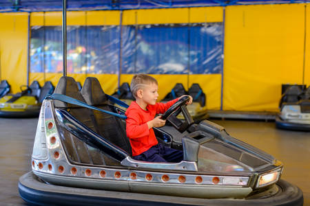 steers: Smiling young boy sitting behind the wheel in a bumper car at an amusement park or fairground as he steers himself around the track