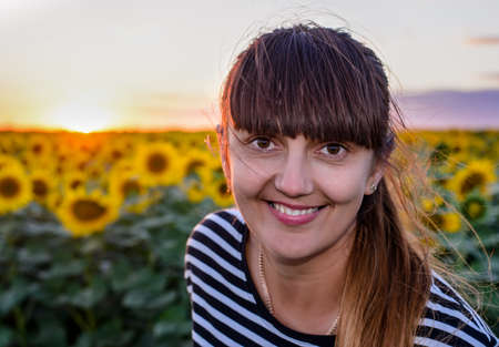 beaming: Smiling woman peering into the lens of the camera with a beaming friendly smile against a background of bright yellow sunflowers at sunset